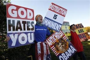Members of the Westboro Baptist Church hold anti-gay signs at Arlington National Cemetery in Virginia on Veterans Day, November 11, 2010. The Supreme Court ruled on Wednesday that a church has the legal right to stage anti-gay protests at military funerals to promote its claim that God is angry at America for its tolerance of homosexuality. REUTERS/Kevin Lamarque